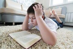 Muchacho que lee un libro mientras que miente en la alfombra en el cuarto Foto de archivo libre de regalías