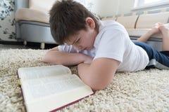 Muchacho que lee un libro mientras que miente en la alfombra en el cuarto Imágenes de archivo libres de regalías