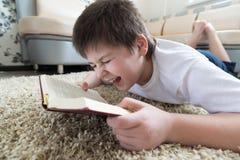 Muchacho que lee un libro mientras que miente en la alfombra en el cuarto Imagen de archivo libre de regalías