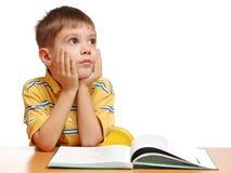 Muchacho que lee un libro y un sueño Fotografía de archivo
