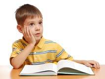 Muchacho que lee un libro y un sueño Foto de archivo