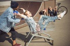 Muchacho que lleva a la muchacha feliz en carro de la compra mientras que amigos que se sientan cerca de rampa Fotografía de archivo