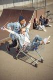 Muchacho que lleva a la muchacha feliz en carro de la compra mientras que amigos que se sientan cerca de rampa Fotos de archivo libres de regalías