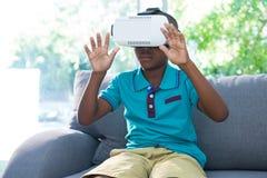 Muchacho que lleva las auriculares de la realidad virtual con los brazos aumentados en casa imagenes de archivo