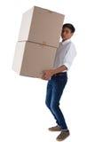 Muchacho que lleva las cajas pesadas Foto de archivo