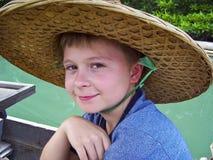 Muchacho que lleva un sombrero fuera de palmtrees Foto de archivo