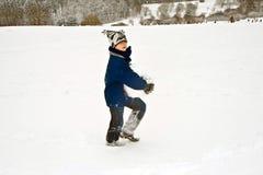 Muchacho que lleva una bola de nieve grande en paisaje hivernal Foto de archivo