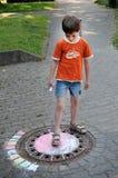 Muchacho que marca la calle con tiza Fotos de archivo