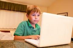 Muchacho que mecanografía en el ordenador portátil blanco Imagen de archivo