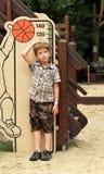 Muchacho que mide su altura en patio Fotografía de archivo