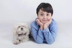 Muchacho que miente al lado de su perro Foto de archivo