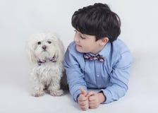 Muchacho que miente al lado de su perro Foto de archivo libre de regalías