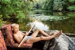 Muchacho que miente en barcos de motor en el río Imagen de archivo libre de regalías