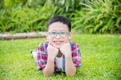 Muchacho que miente en campo y sonrisas de hierba Fotografía de archivo libre de regalías