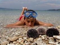 Muchacho que miente en el mar con los erizos de mar Fotografía de archivo libre de regalías