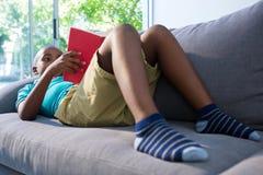Muchacho que miente en el sofá mientras que lee la novela en casa fotografía de archivo libre de regalías