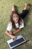 Muchacho que miente en hierba con la computadora portátil y que mira para arriba Imagenes de archivo