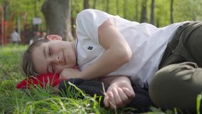 Muchacho que miente en la hierba en el parque cerca del trastorno del patio o cansado despu?s de escuela en un d?a caliente del f almacen de metraje de vídeo