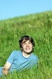 Muchacho que miente en la hierba verde fresca Fotos de archivo libres de regalías