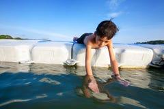Muchacho que miente en la plataforma flotante en el mar que intenta coger la pequeña gamba Fotos de archivo libres de regalías