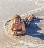 Muchacho que miente en la playa Imágenes de archivo libres de regalías