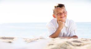 Muchacho que miente en la playa en el tiempo soleado Fotos de archivo libres de regalías