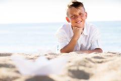 Muchacho que miente en la playa en el tiempo soleado Foto de archivo libre de regalías