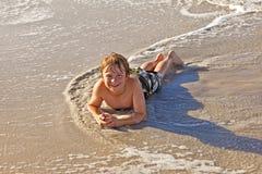 Muchacho que miente en la playa y que goza del sol Foto de archivo