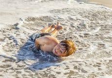 Muchacho que miente en la playa y que goza del sol Fotografía de archivo