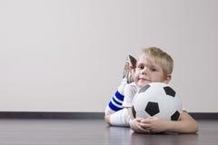 Muchacho que miente en piso con el balón de fútbol Fotografía de archivo