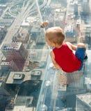 Muchacho que mira abajo la ciudad de un skyscarper Foto de archivo libre de regalías