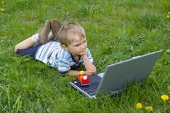 Muchacho que mira adentro al ordenador Fotografía de archivo libre de regalías