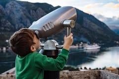 Muchacho que mira con binocular la ciudad de Kotor, Montenegro Imagen de archivo libre de regalías