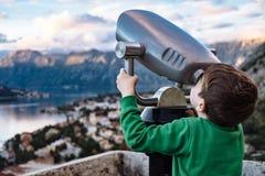 Muchacho que mira con binocular la ciudad de Kotor, Montenegro Fotos de archivo