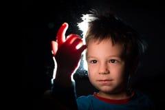 Muchacho que mira con gran curiosidad su mano en un rayo de la luz Imágenes de archivo libres de regalías