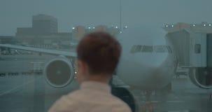 Muchacho que mira el avión a través de la ventana del aeropuerto almacen de video