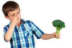 Muchacho que mira el bróculi con repugnancia imagen de archivo