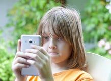 Muchacho que mira el teléfono móvil Imagen de archivo