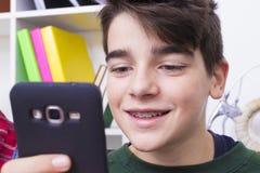 Muchacho que mira el teléfono móvil y la sonrisa Fotos de archivo libres de regalías