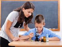 Muchacho que mira en el microscopio Fotografía de archivo libre de regalías
