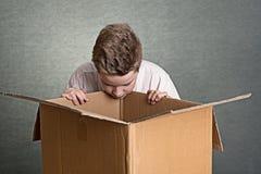 Muchacho que mira en una caja de cartón grande Fotos de archivo libres de regalías