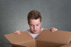 Muchacho que mira en una caja de cartón grande Imagenes de archivo