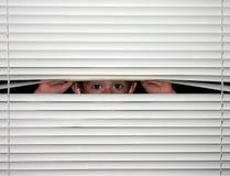 Muchacho que mira a escondidas hacia fuera Imagen de archivo