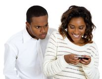 Muchacho que mira furtivamente en el teléfono móvil de las muchachas Foto de archivo