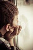 Muchacho que mira hacia fuera la ventana con el icono del corazón sobre el vidrio Fotos de archivo libres de regalías