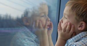 Muchacho que mira hacia fuera la ventana del tren con las manos en almacen de metraje de vídeo
