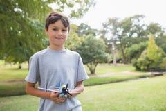 Muchacho que mira la cámara y que celebra un avión del juguete en el parque Foto de archivo libre de regalías
