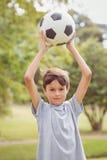 Muchacho que mira la cámara y que sostiene un balón de fútbol en el parque Foto de archivo libre de regalías