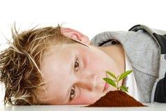 Muchacho que mira la planta en suelo Fotografía de archivo