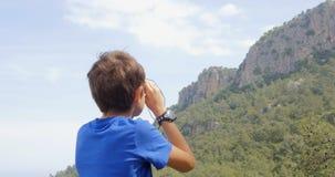 Muchacho que mira las montañas almacen de video